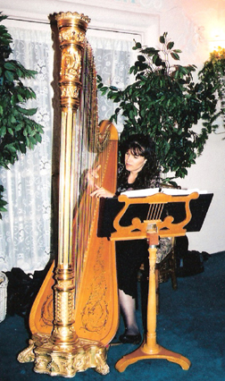 Pamela Brown performing on her harp at a dinner party.
