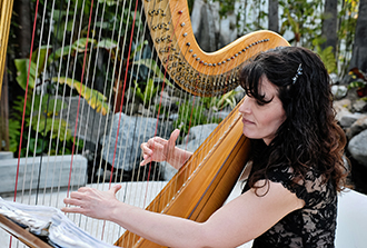 Photo of Pamela Brown performing with her harp at a wedding.